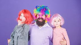 Just for fun. Party time. How crazy is your father. Man bearded father and kids girls wear colorful wig violet royalty free stock photos