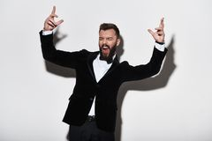 Just going crazy. Handsome young man in full suit making a face. And gesturing while standing against grey background Royalty Free Stock Images