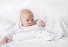 Just hanging... Cute baby enjoying the silence in white blankets royalty free stock photos