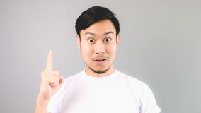 Just have a interresting idea. An asian man with white t-shirt and grey background royalty free stock image