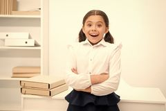 Just heard excellent news. Child girl wears school uniform standing excited face expression. Schoolgirl smart child. Looks excited white interior background royalty free stock image