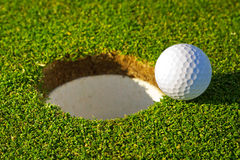 Just at the hole. Golf ball near the hole Stock Photo