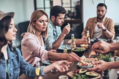 Just hungry. Group of young people in casual clothing eating while having a dinner party indoors royalty free stock photography