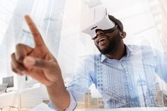 Curious man wearing virtual glasses. Just imagine. Close up of young curious man wearing virtual glasses while putting forward his finger and expressing interest Royalty Free Stock Photos