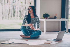 Just inspired. Confident young beautiful woman holding coffee cup and smiling while sitting on the floor at home with blueprint laying near her Stock Images