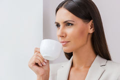 Just inspired. Confident young businesswoman in suit drinking coffee and looking away while leaning at the wall Stock Image