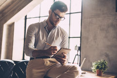 Just inspired. Confident young man in smart casual wear writing something in his notebook while leaning at the desk in office Stock Image
