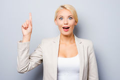 Just inspired. Excited young businesswoman pointing up while standing against grey background Royalty Free Stock Photo