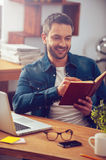 Just inspired. Handsome young man looking at his notebook and smiling while sitting at his working place in office Royalty Free Stock Photography