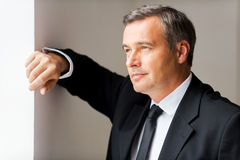 Just inspired. Thoughtful mature man in formalwear looking away while leaning at the wall Royalty Free Stock Photos