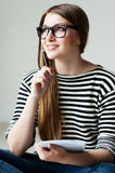 Just inspired. Thoughtful young woman in striped clothing holding note pad and touching her chin with pen while sitting on the hardwood floor Royalty Free Stock Images