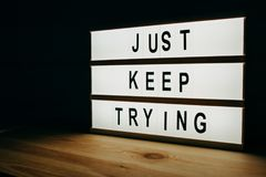Just keep trying. Motivational message on lightbox stock images