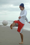 Just kicked. Boy playing. Just kicked the beach soccer ball Royalty Free Stock Photography