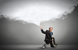 Just like a child. Young funny businessman riding three wheeled bicycle Royalty Free Stock Photo