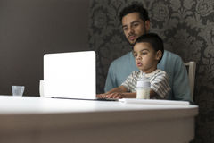 Just like daddy does. Young father is sitting at the table with his son on his lap. His son is copying his dad and exploring his curiosity by pressing buttons Stock Photos