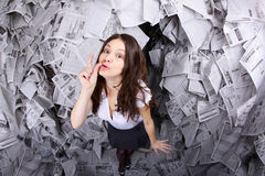 Just a little bit of news. Fish eye portrait of business woman showing a sign with the hand surrounded by newspapers everywhere Royalty Free Stock Photography