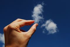 Just A Little Pinch - Left Hand. Left fingers appear to be pinching a white cloud with blue sky in the background Royalty Free Stock Photography