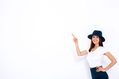 Just look at that!. Beautiful young woman pointing up and smiling while standing against white background Royalty Free Stock Images