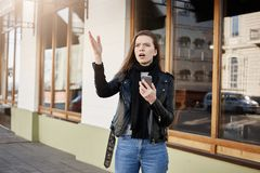 Just look at this building. Attractive young woman in trendy leather coat pointing with palm aside while looking up and. Holding smartphone, walking along Royalty Free Stock Photos