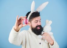 Just look at that egg. Bearded man with bunny toy and Easter egg. Easter bunny delivering colored eggs. Celebration of. Spring time holiday. Hipster with long royalty free stock images
