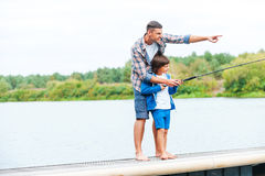 Just look at that!. Father and son fishing together while standing on quayside together Stock Photography