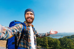 Just look! I am here!. Handsome young man carrying backpack and taking a picture of himself and pointing to the view stock images