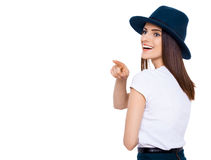 Just look over there!. Happy teenage girl pointing away and smiling while standing isolated on white Stock Images