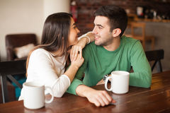 Just looking at each other. Young happy couple relaxing together and looking at each other while having some coffee in a restaurant Stock Images