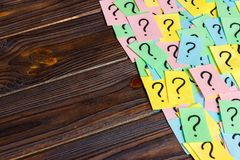 Just a lot of question marks on colored papers on wood background.  Stock Photo