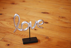 Just Love. A metal cast love lettering on a stand, placed on a natural wooden floor Stock Images