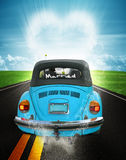 Just married. A blue convertible volkswagen beetle with Just Married on the window.  The car is traveling down an asphalt road into a heart shaped cloud.  Heart Stock Image