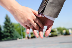 Just Married. Groom's hand holding bride's hand with a wedding bands Stock Photography