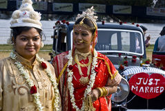 Just Married. Two young Indian girl are posing with traditional Indian marriage dressings in front of a vintage car in a vintage car fashion show in Kolkata Stock Photos