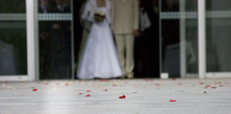 Just Married. A newly wed couple waling out of a building Royalty Free Stock Photo