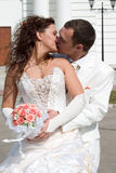 Just married. Kiss of young couple in wedding wear with bouquet of roses Stock Photo