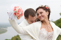 Just married. Young couple in wedding wear with bouquet of roses Royalty Free Stock Photo