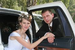 Just married. Bride and bridegroom are taken pictures beside limousine Stock Photography