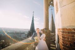 Just married bride and groom holding each other on the balcony of old gothic cathedral. High tower spires at background Royalty Free Stock Image