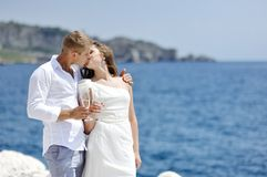 Just married bride and groom kissing near sea in wedding day Stock Image