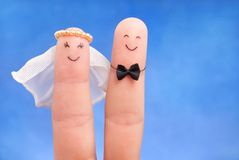 Just married concept -  newlyweds painted at fingers against blu Stock Image