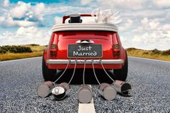 Just Married convertible on a road. A newlywed couple is driving a retro car with just married sign and cans rear view 3D rendering stock images