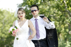 Just married couple. Posing on a road against green trees stock photo