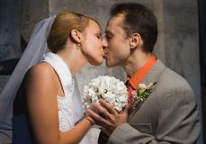 Just married couple. Kissing holding a round bouquet of white flowers Royalty Free Stock Image