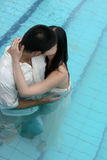 Just married couple. Bride and groom in the swimming pool - trash the dress trend Royalty Free Stock Image