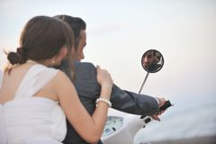 Just married couple on the beach. Wedding sce of bride and groom just married couple on the beach ride white scooter and have fun Royalty Free Stock Image