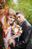 Just married couple with beautiful red autumn leaves Stock Image