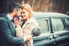 Just married couple at the black retro car on their wedding. stock images