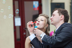 Just married couple blow bubbles Royalty Free Stock Images