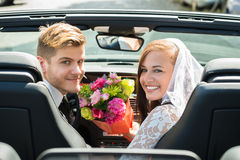 Just Married Couple With Bouquet In The Car. Young Smiling Just Married Couple With Bouquet In The Car stock image