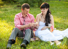Just married couple changing rings on meadow Royalty Free Stock Photos